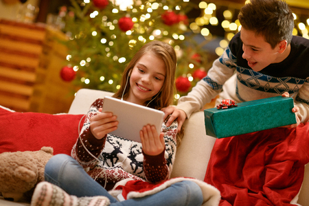 Cheerful young boy and girl enjoying in music Christmas gifts