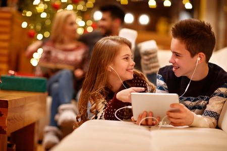 陽気な少女と一緒にタブレットで音楽を聞いている少年