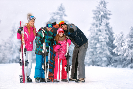 Happy family with ski equipment looking something together