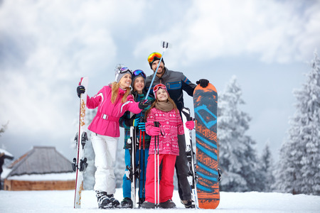 Skiing family enjoying winter vacation on snow in cold day and making mobile selfie in mountains