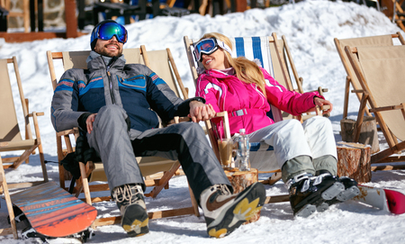 happy couple at mountains in winter laughing and relax in sunbed