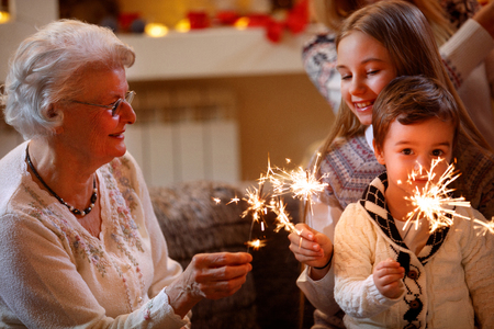 smiling grandchildren and grandparents with sprinklers celebrating xmas