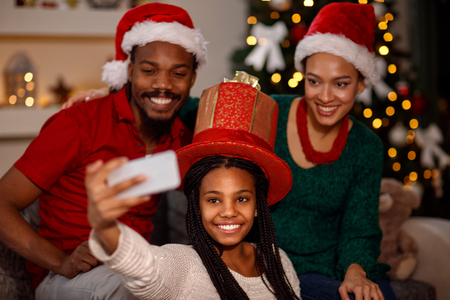 Cute little girl with her parent taking selfie on Christmas