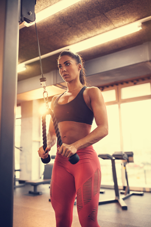 Fit woman in fitness center exercise arms muscles on equipment