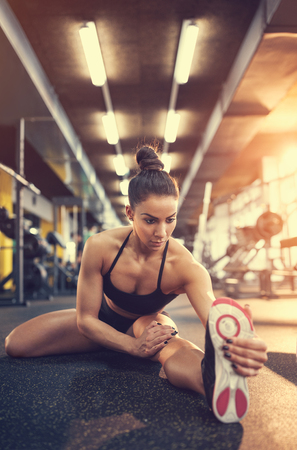 Attractive female doing exercise for stretching legs in gym Reklamní fotografie