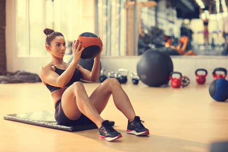 Fit sportswoman doing exercise with ball for six pack Stock Photo