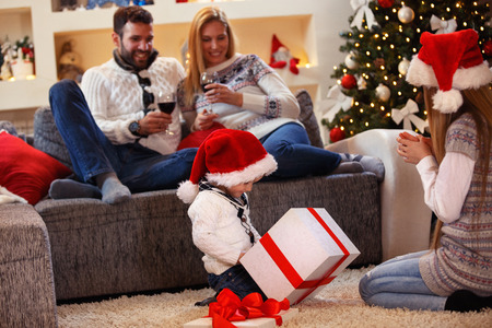 Christmas present - happy children opens present with family  Stock Photo