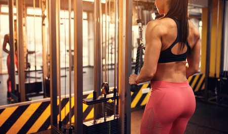 Athletic woman shaping body muscles in gym
