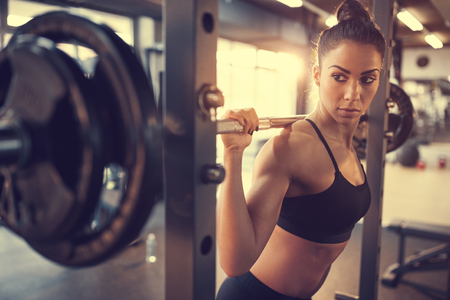 Young female doing exercise with barbell in fitness club