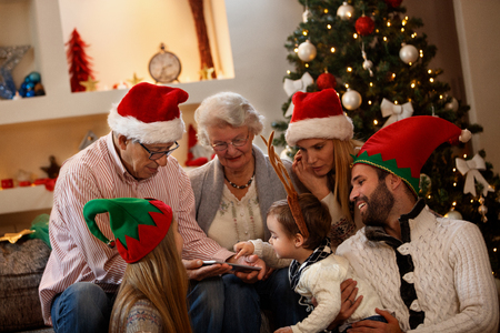 Children with grandparents looking  Christmas photos on cell phone
