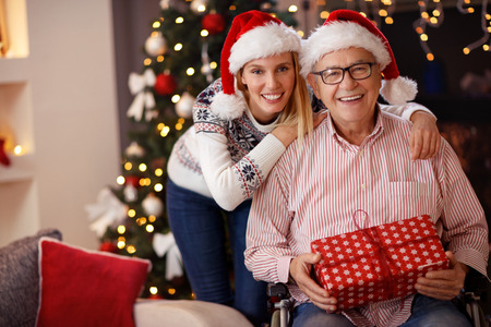 smiling daughter and elderly father in wheelchair celebrating Christmas together