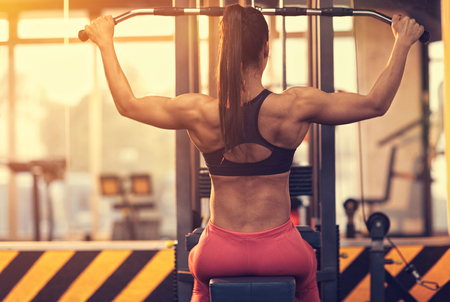 Athletic woman using machine for pumping  back muscles in gym, back view