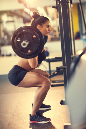 Female athlete doing squats with barbell in fitness center Foto de archivo