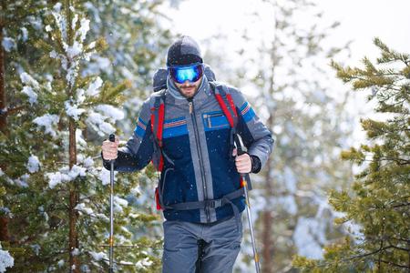 Young sportsman hiking in winter with snow thru wood 版權商用圖片