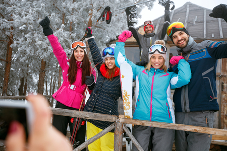 Smiling friends spend winter holidays at mountain cottage and having fun