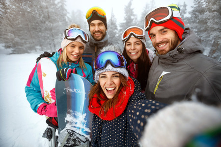 winter, extreme sport and people concept - happy friends having fun on the snow and making selfie