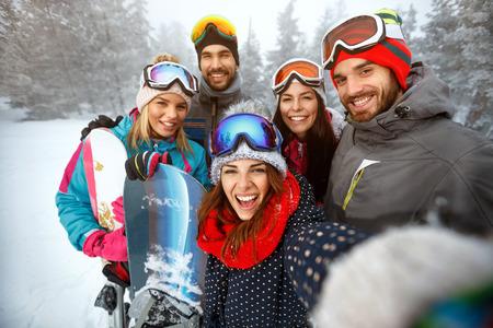 winter, extreme sport en mensenconcept - gelukkige vrienden die pret in de sneeuw hebben en selfie maken Stockfoto