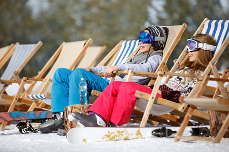 Brother and sister sitting in sun loungers on ski terrain