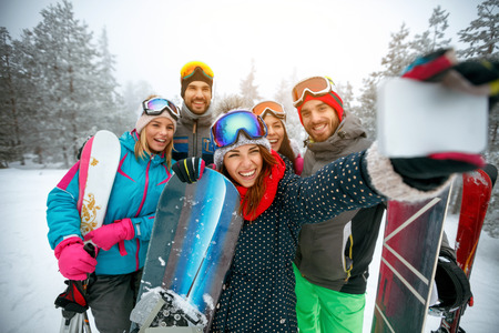 winter, extreme sport and people concept - Group of smiling friends making selfie on the snow