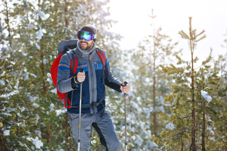 Man hiking at winter in snowy wood