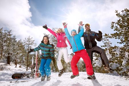 山では雪の上でジャンプ スキーの幸せな家族