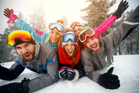 Group of friends on winter holidays – Happy skiers lying on snow and having fun  Banque d'images