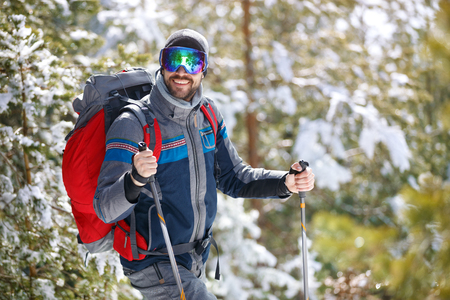 Smiling man in action with hiking equipment