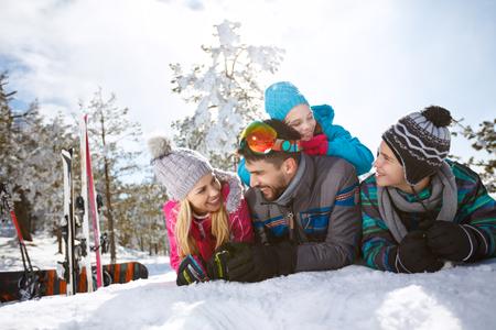 冬の休暇で雪の上に横たわって若い子供連れの家族