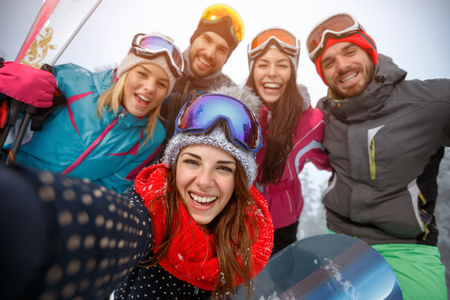 Group of smiling friends having fun on the snow and making selfie