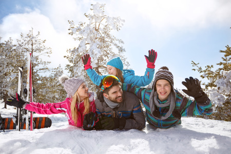 Happy family having fun on snow on winter holiday