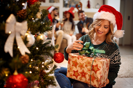 Happy young girl in Santa's hat with Christmas presents at home