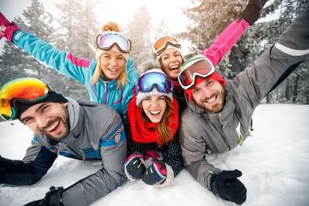 Gruppo di sciatori maschio e femmina godendo insieme sulla neve in montagna