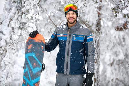 Male snowboarder with ski equipment at winter vacation 版權商用圖片