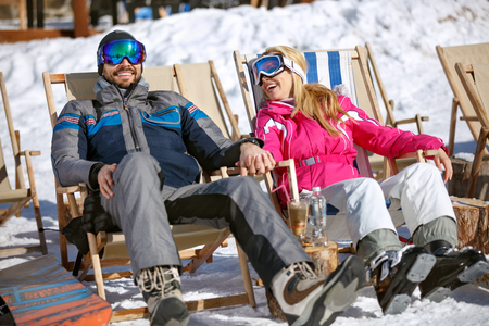 Happy man and woman skiers sitting in sun lounger on ski terrain