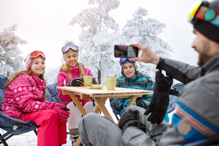 Man on ski terrain making family photo while resting in cafe
