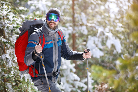 Smiling hiker with equipment hiking thru forest