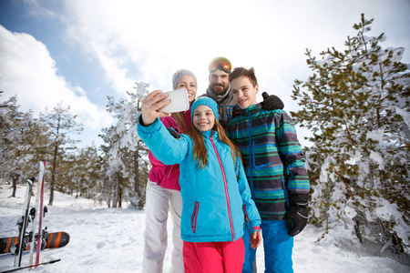 Girl with family on skiing taking photo with cell phone