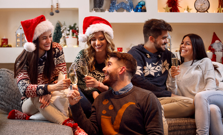 Happy friends toast with champagne and celebrating Christmas Stock Photo