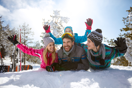 Cheerful parents with children on snow at winter vacation