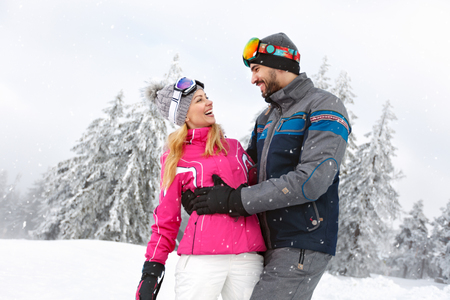 Cheerful man and woman in love enjoy together in snowy nature