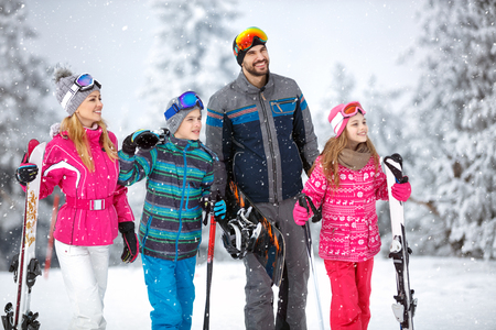 Cheerful family on winter holiday going to ski terrain