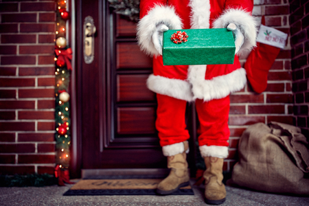 Close up of Christmas gift in Santa Claus hands in front of door, concept