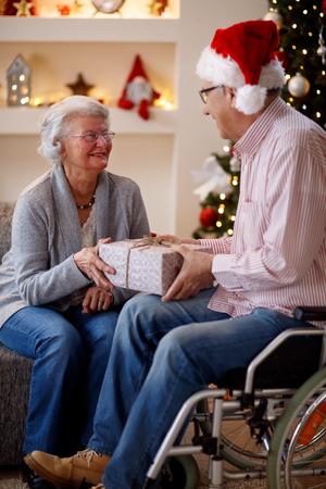 Smiling elderly couple sharing Christmas gifts Stock Photo