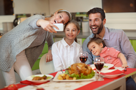 Young happy family taking photo with mobile phone for Christmas  Stock Photo