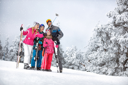 Happy woman with family together making  selfie in mountain at skiing