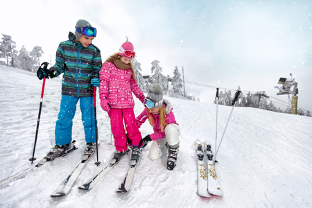 Young mother helps to daughter to properly puts ski shoes on skis on ski terrain