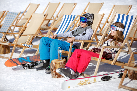 Boy and girl sitting in sun lounger on ski terrain and resting 版權商用圖片