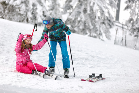 Young brother helps his sister to get up from ski terrain with skis Stock Photo