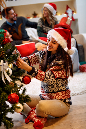 Happy young woman in Santa hat decorating a Christmas tree