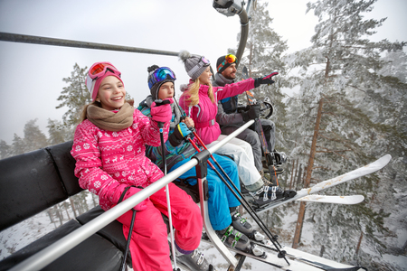 スキー場のスキー場のリフトの持ち上げで幸せな家族